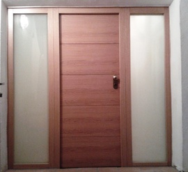 puerta entrada vivienda acorazada con fijos laterales con cristal de seguridad, en Roble, exterior